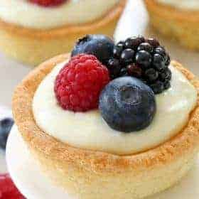 Berry Cookie Cups have a sugar cookie crust and white chocolate cream cheese filling! Top them with fresh berries for the perfect summer dessert. Recipe contains gluten-free option.