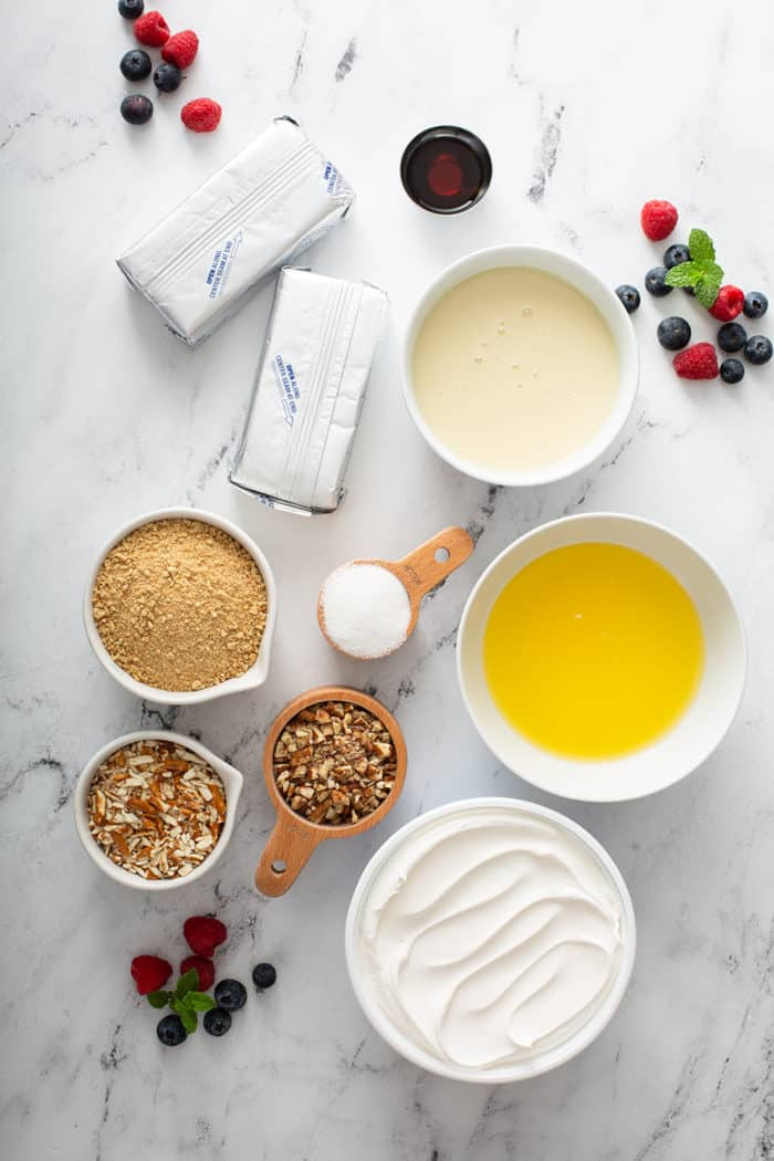 Ingredients for no-bake frozen cheesecake arranged on a marble countertop