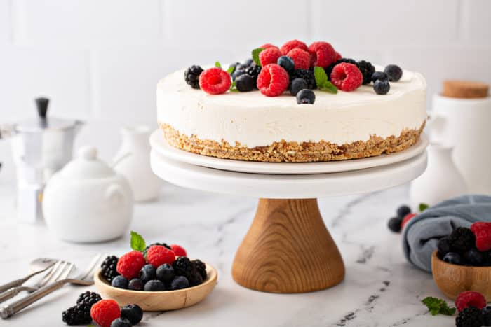 No-bake frozen cheesecake topped with mixed berries, set on a wooden cake stand