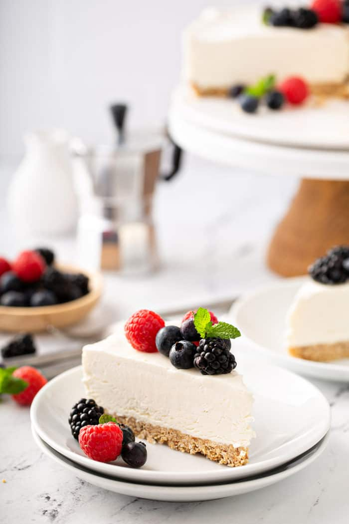 Slice of no-bake frozen cheesecake plated on a white plate, topped with mixed fresh berries. Additional slices of cheesecake are in the background