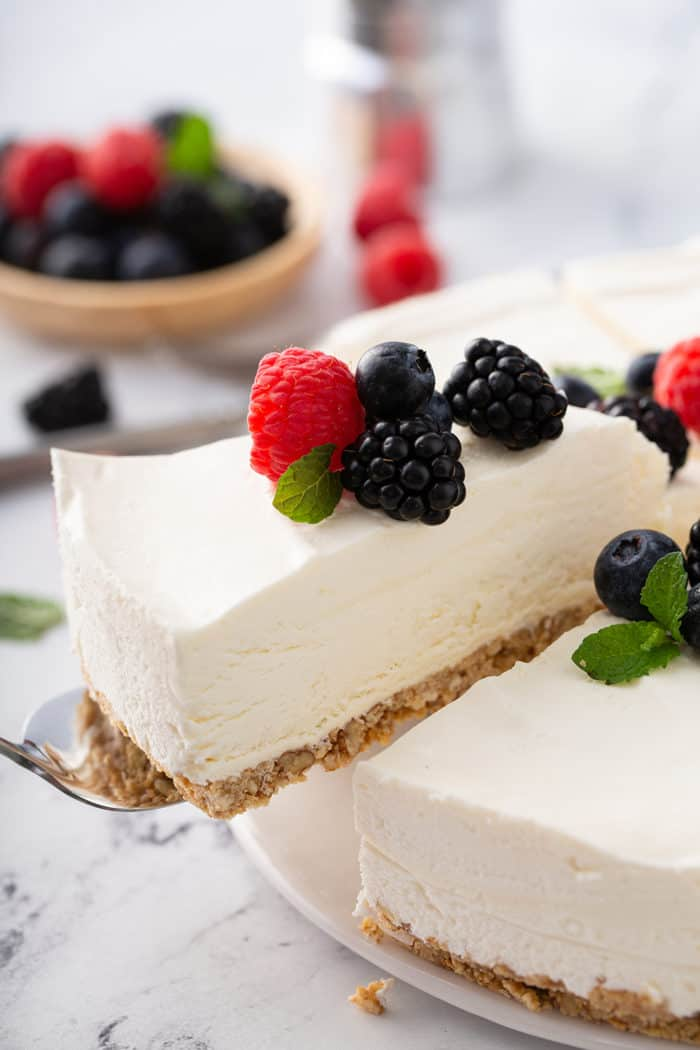 Pie server pulling a slice of no-bake frozen cheesecake out of the full cheesecake