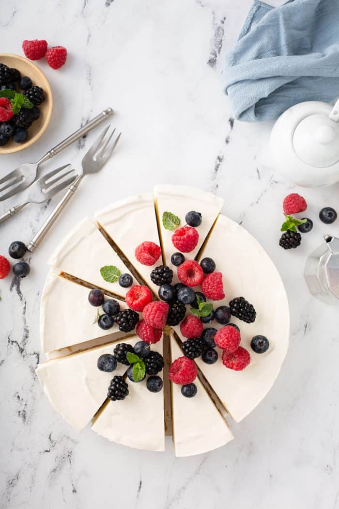 Overhead view of a sliced no-bake frozen cheesecake, garnished with fresh mixed berries