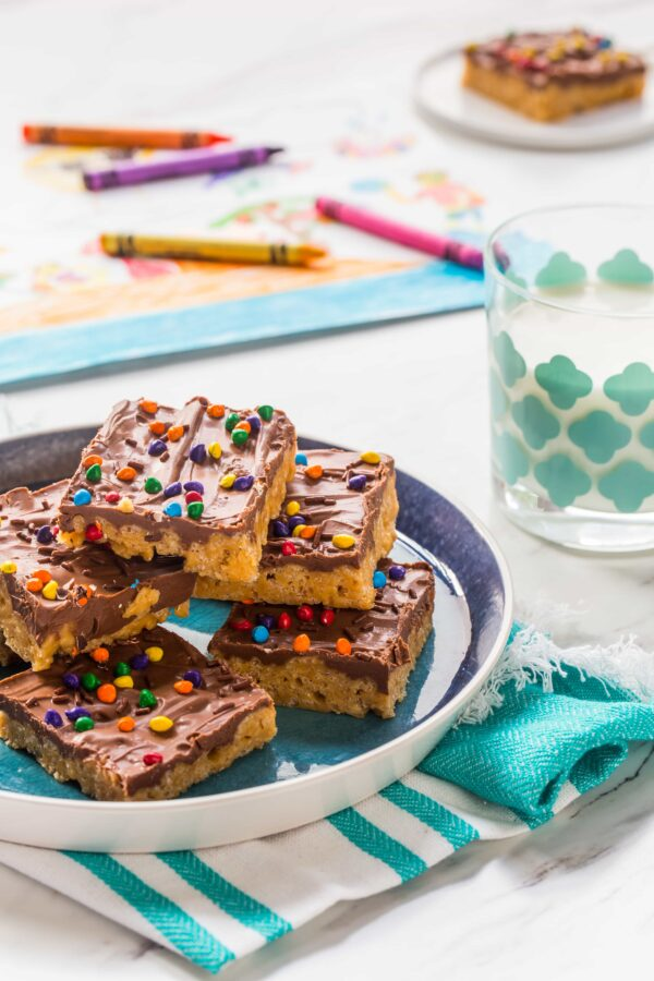 Chocolate Scotcheroos combine peanut butter, crispy rice cereal, and chocolate into one delicious treat. A perfect recipe to whip with your kids!