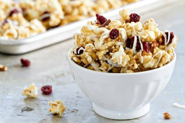 Maple Caramel Corn with marshmallows, chopped pecans, dried cranberries, and a decadent drizzle of white chocolate. THIS is the caramel corn you'll want to make and eat, all fall long.