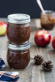 Two small jars of apple butter stacked on top of each other on a wood table