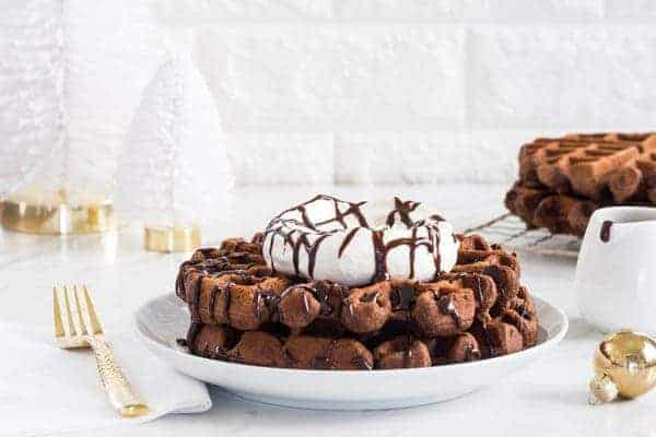 Chocolate Eggnog Waffles are a warm and cozy way to welcome the holiday season. Take them over-the-top with whipped cream and chocolate sauce.