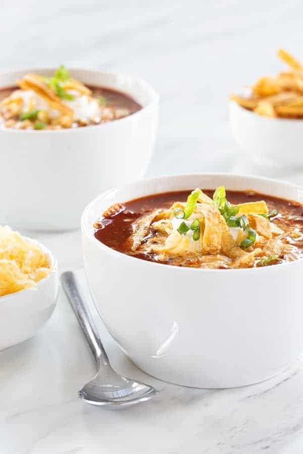 Slow Cooker Taco Soup uses up all your fresh and frozen veggies for a hearty dinner. Serve it up with tortilla strips, shredded cheese, and sour cream.