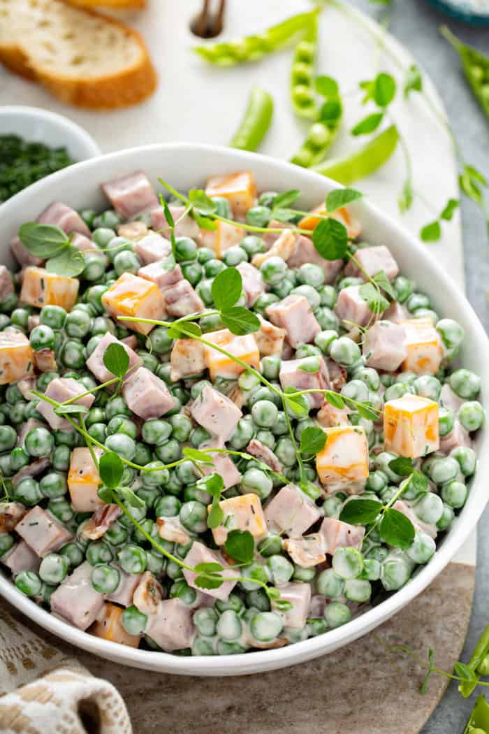Close up of a bowl of Amish Pea Salad garnished with fresh herbs