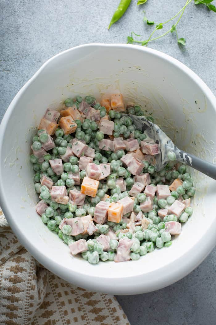 Spatula stirring together Amish pea salad in a white mixing bowl