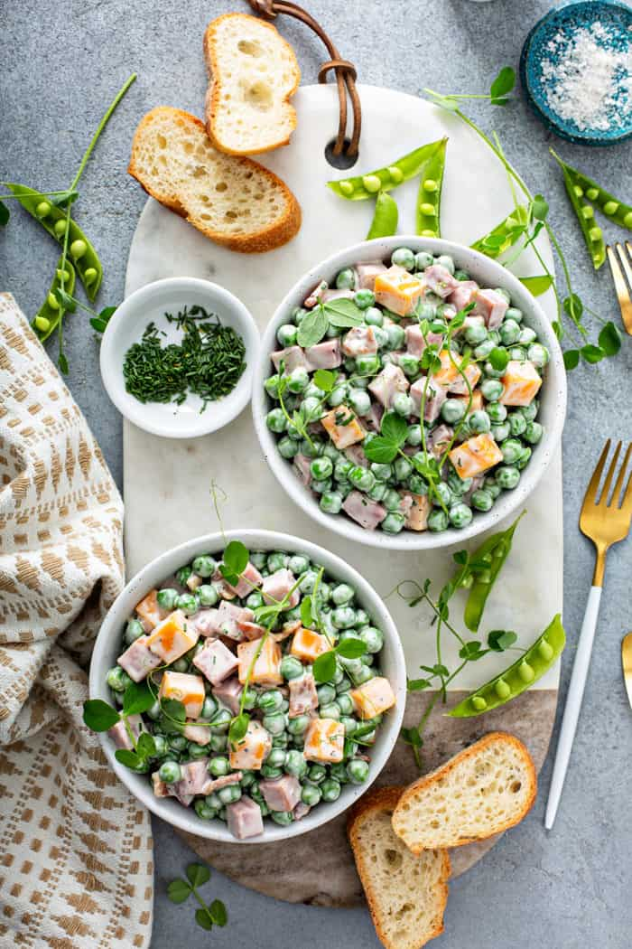 Overhead view of two small bowls of Amish pea salad on a white board surrounded by fresh peas, chives, and baguette slices