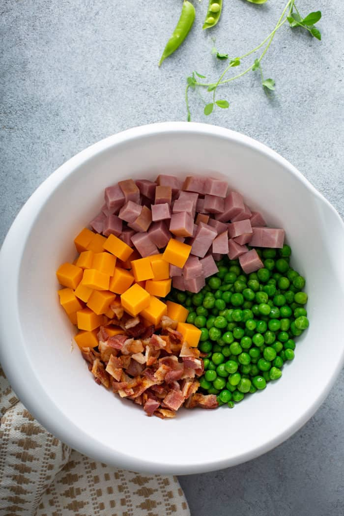 Green peas, cheddar cheese, ham, and bacon in a white mixing bowl