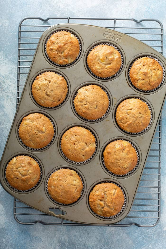 Baked hummingbird cupcakes in a muffin tin, set on a wire cooling rack