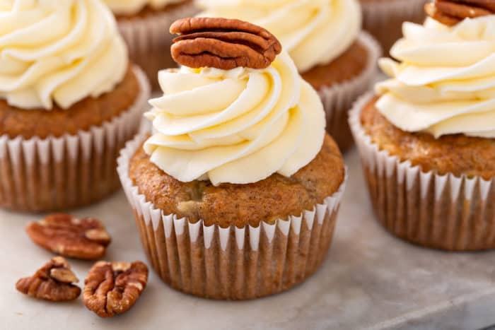 Close up of a frosted hummingbird cupcake topped with a pecan half