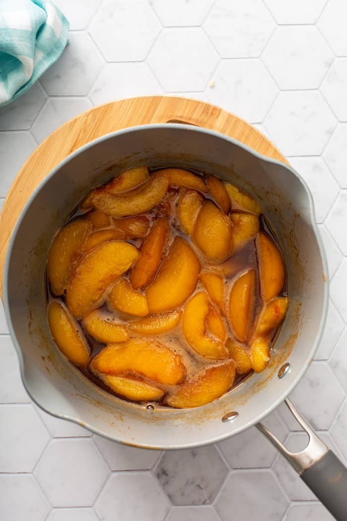 Peach compote in a saucepan set on a wooden trivet