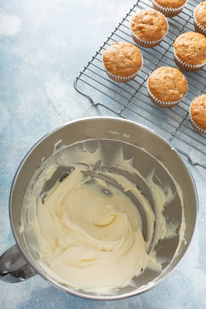 Bowl of cream cheese frosting on a blue countertop next to hummingbird cupcakes on a wire cooling rack