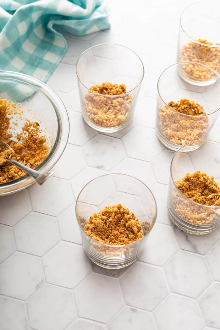 Crust for no-bake peach cheesecakes being added to the bottom of individual serving dishes