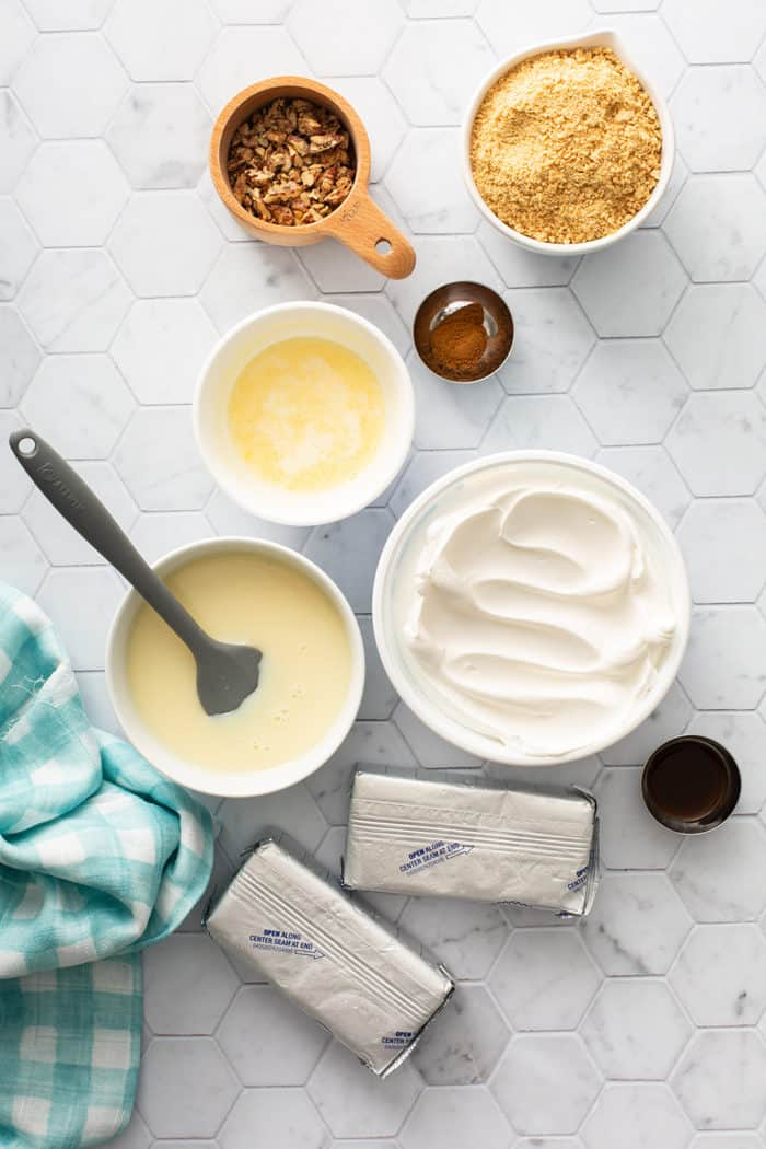 No-bake cheesecake ingredients on a white tiled countertop