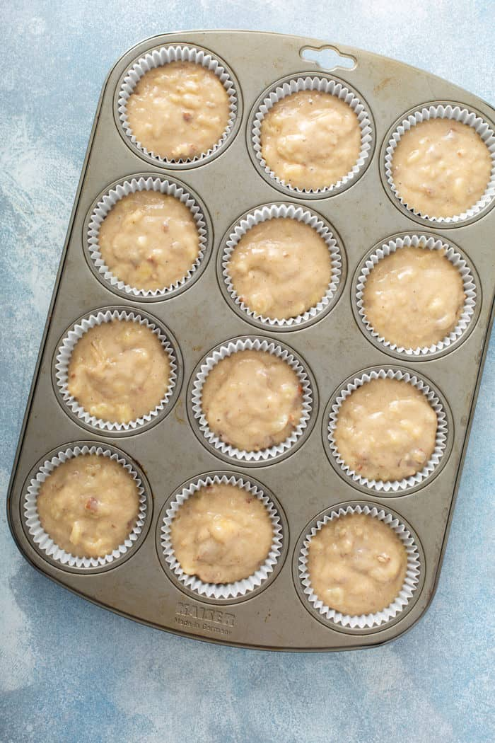 Batter for hummingbird cupcakes in a muffin tin, ready to bake