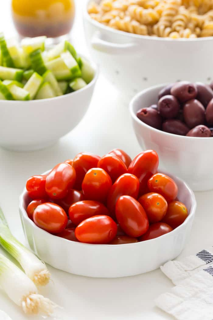 Close up of a bowl of grape tomatoes with other veggies in the background