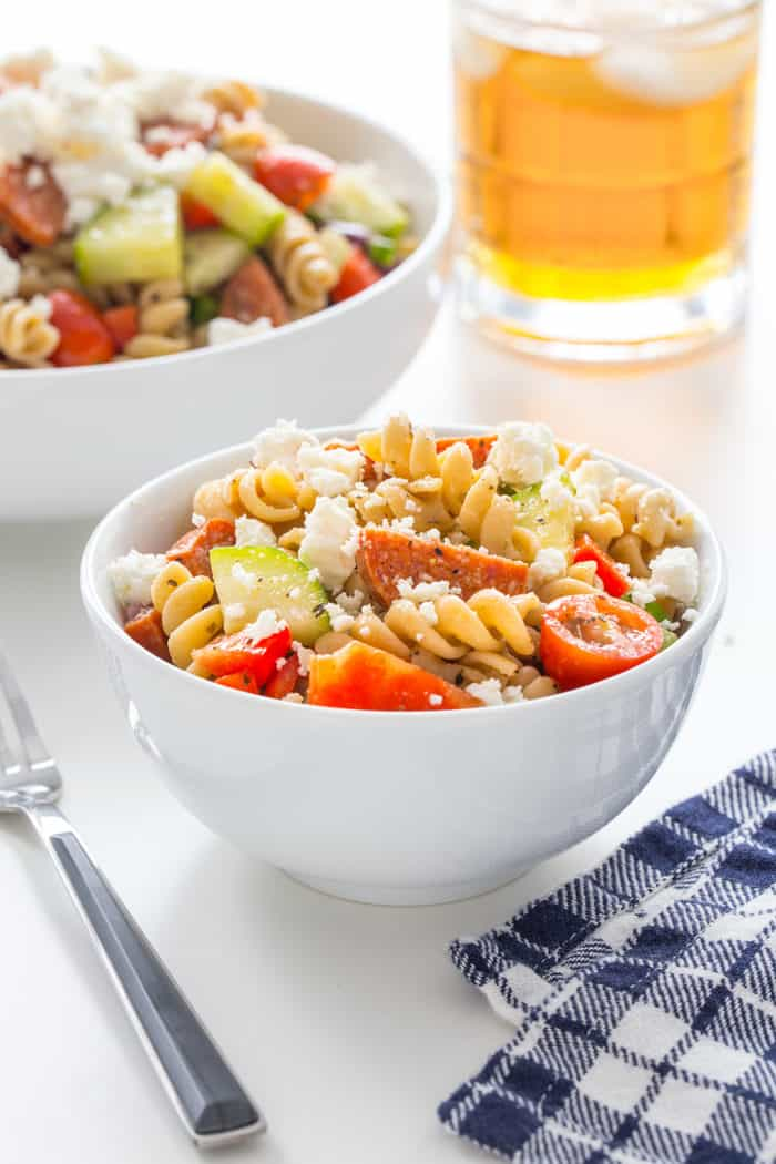Greek pasta salad in a small white bowl next to a blue napkin on a white countertop