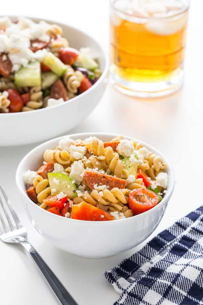 Small bowl of greek pasta salad with a larger serving bowl in the background