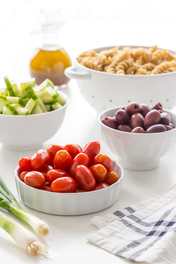 Bowls of fresh vegetables for greek pasta salad arranged on a white countertop