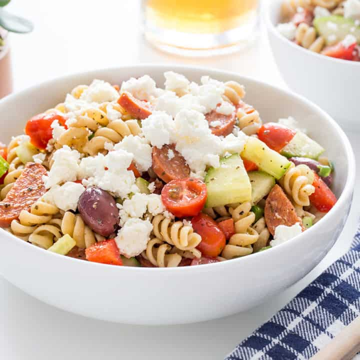 Greek pasta salad in a white serving bowl on a white countertop