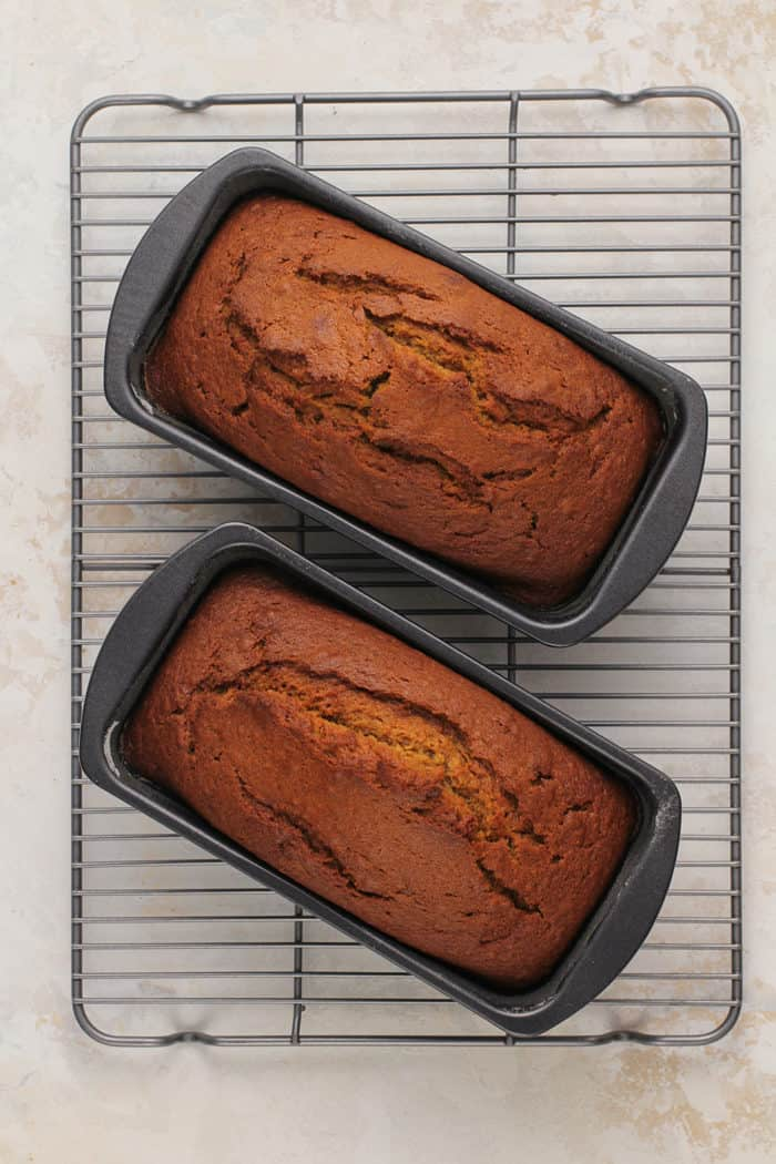 Two baked loaves of pumpkin bread cooling on a wire rack