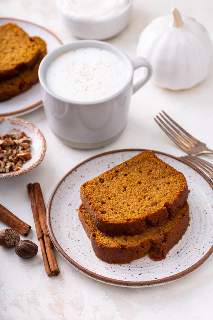 Two slices of pumpkin bread on a plate next to a cup of coffee