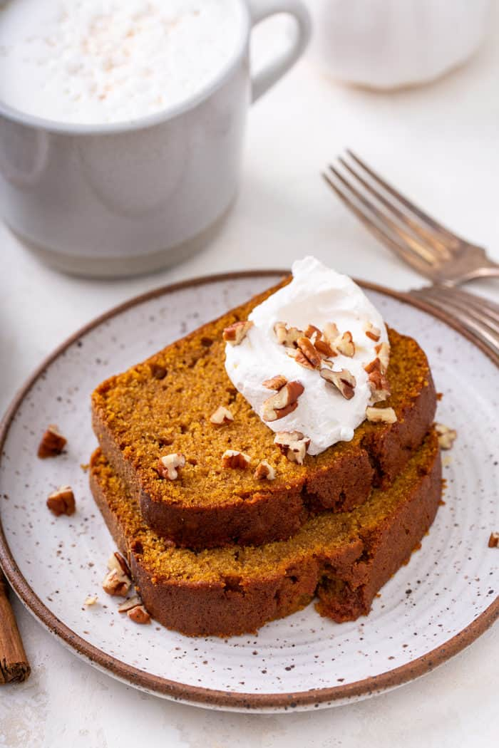 Two slices of pumpkin bread topped with whipped cream on a plate