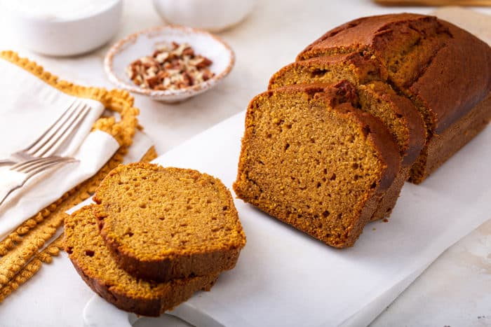 Slices of pumpkin bread on a white cutting board