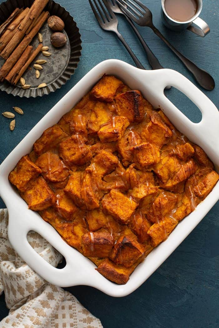 Overhead view of baked pumpkin bread pudding in a white baking dish