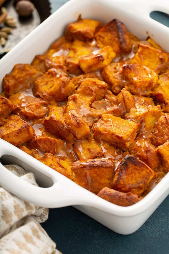 Close-up of baked pumpkin bread pudding in a white baking dish
