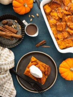 Overhead view of a plated slice of bread pudding next to a baking dish of pumpkin bread pudding