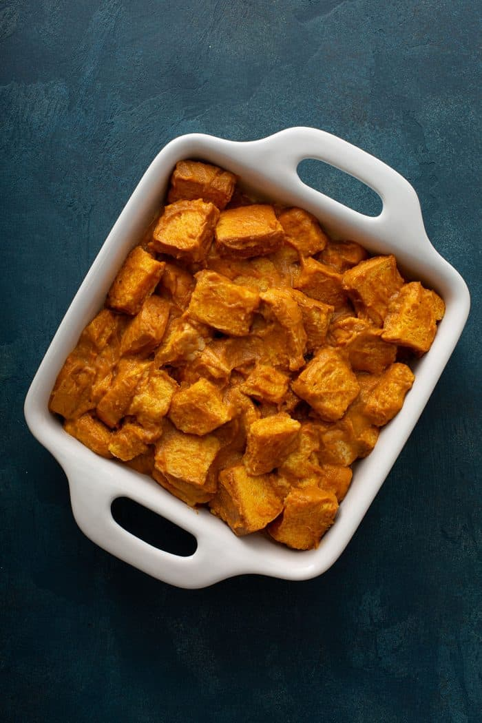 Pumpkin bread pudding in a white baking dish, ready to be baked