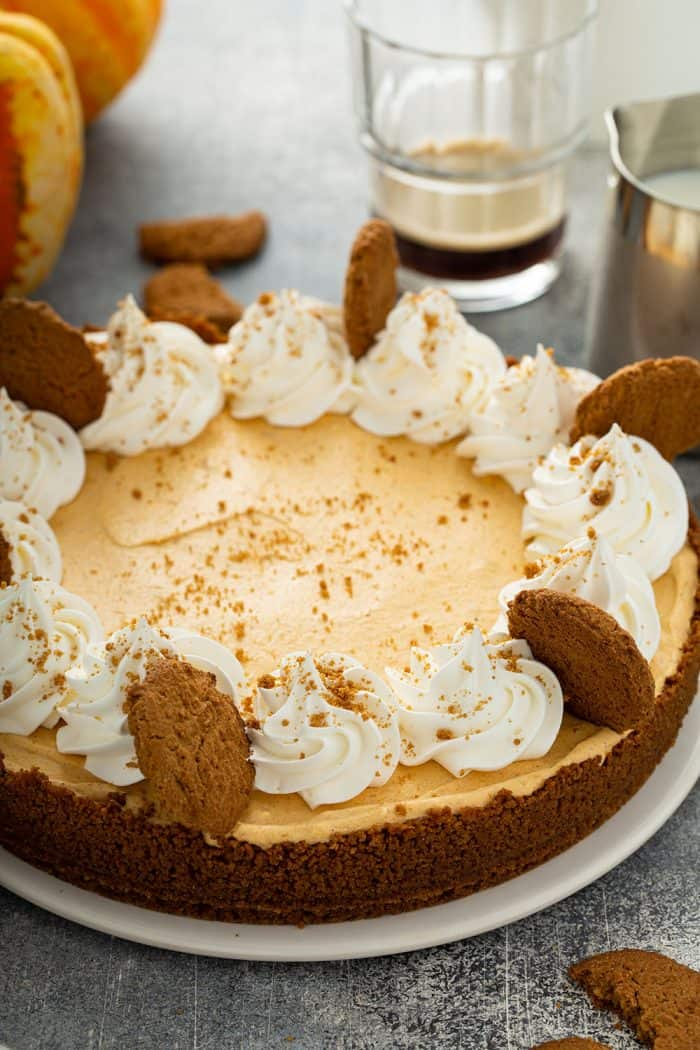 Assembled marshmallow pumpkin pie garnished with whipped cream and gingersnap cookies