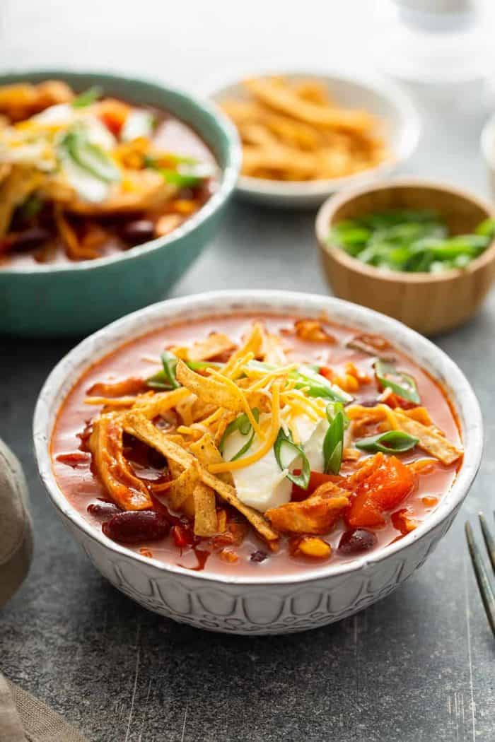 Close up of chicken chili topped with sour cream and cheese in a white bowl