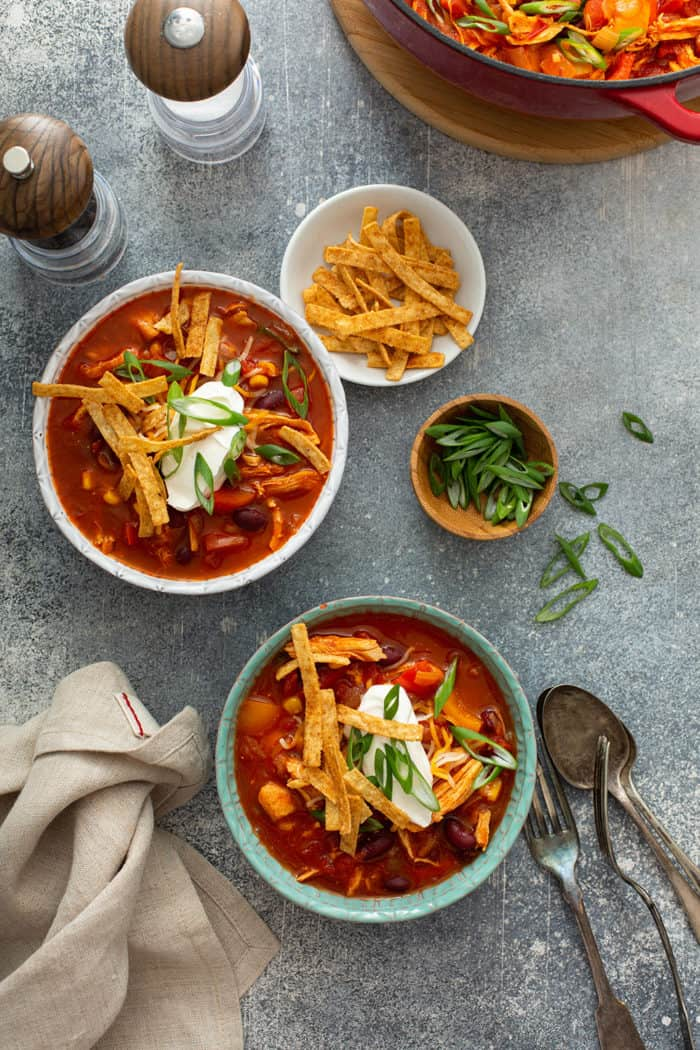 Overhead view of two bowls of easy chicken chili surrounded by bowls of toppings