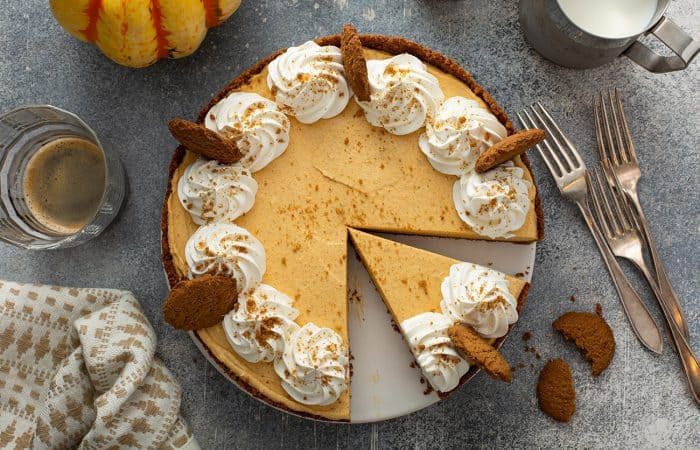 Overhead view of sliced marshmallow pumpkin pie on a gray counter