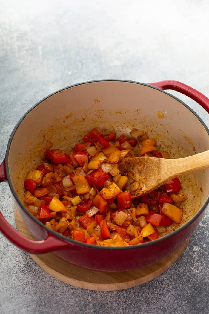 Wooden spoon stirring sauteed peppers with spices in a dutch oven