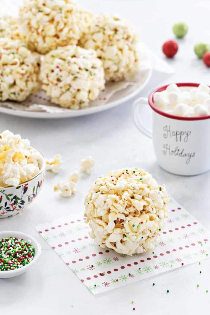 Popcorn Balls are a fun and delicious way to celebrate the season. This simple recipe is a great base for so many flavor combinations. A fun and sweet holiday tradition!