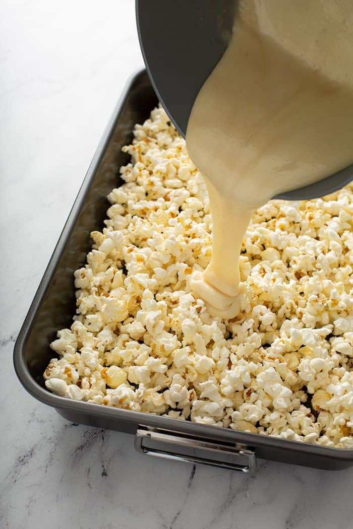 Light caramel being poured over a pan of popped popcorn