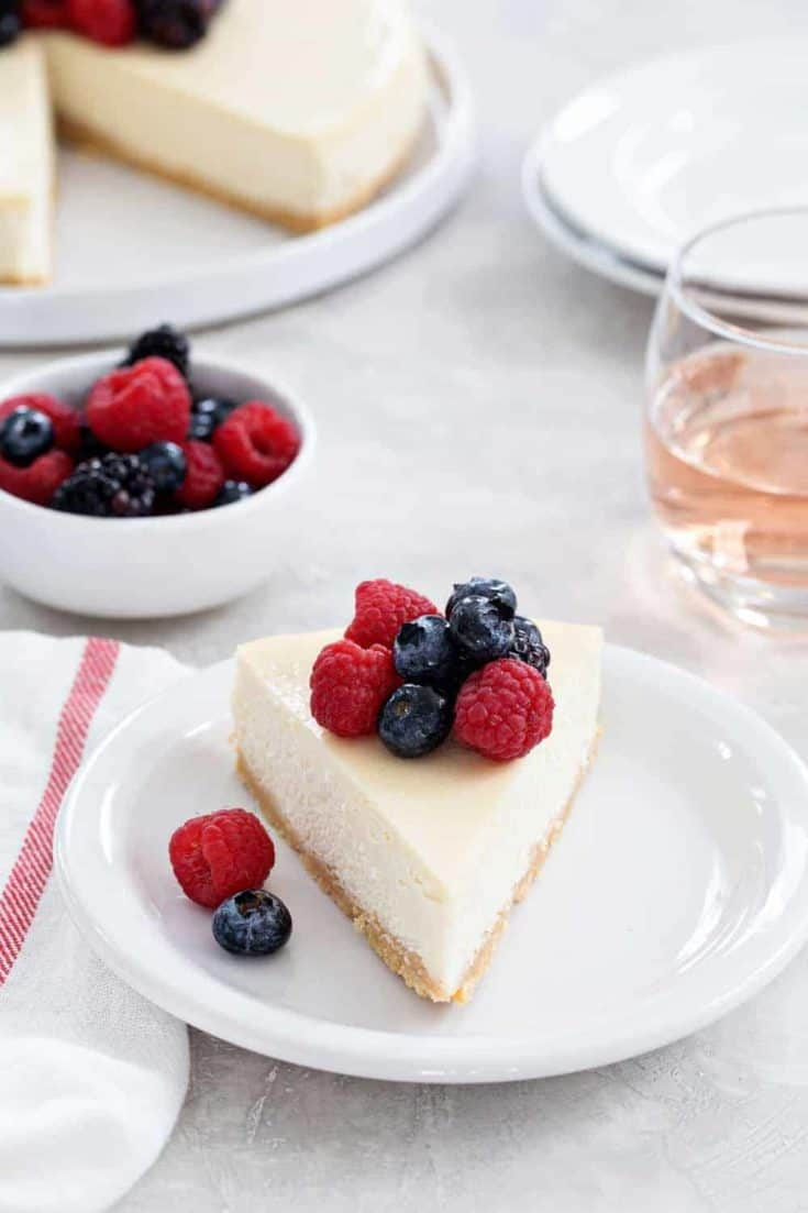 Rosé Cheesecake is smooth, creamy, and full of delicious flavors. A sugar cookie crust and rosé soaked berries make it totally irresistible.