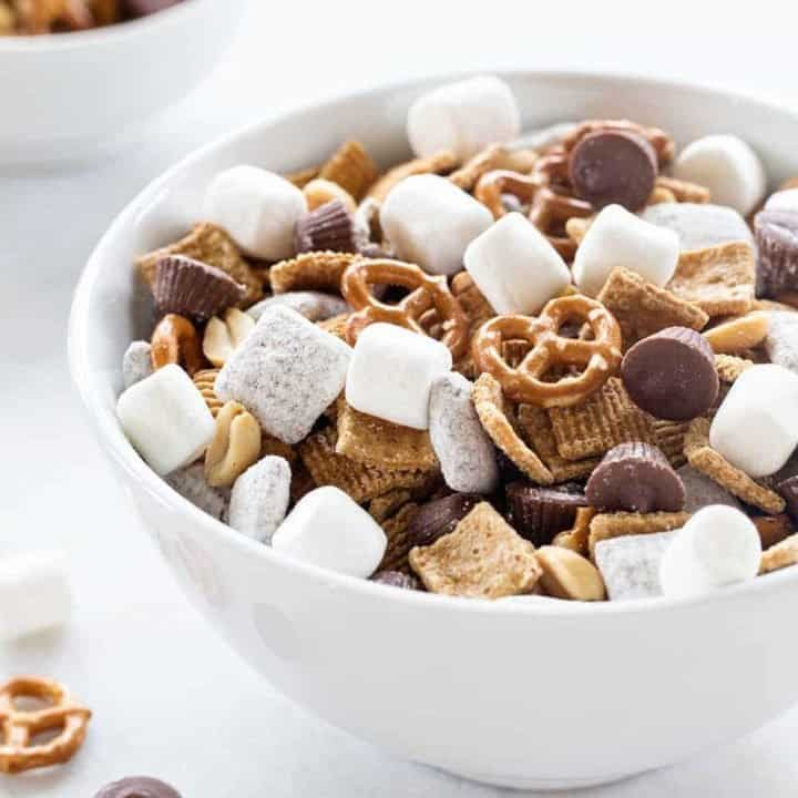 S'mores Snack Mix combines graham cereal, puppy chow, pretzels, peanuts, mini peanut butter cups and marshmallows to create the most amazing snack mix! You're going to LOVE it!