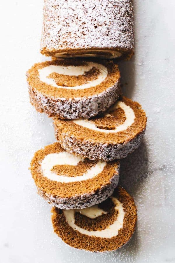 Overhead shot of a sliced pumpkin roll dusted with powdered sugar