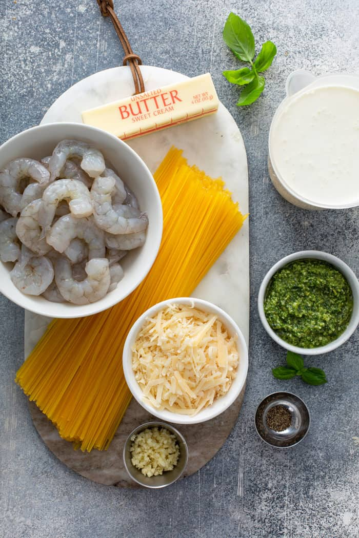 Ingredients for creamy pesto pasta with shrimp on a gray counter