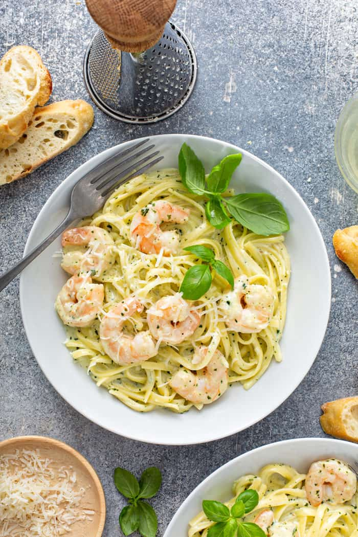 Overhead view of a fork set in a bowl of creamy pesto pasta with shrimp, garnished with fresh basil