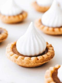 Close up of a mini pumpkin pie topped with whipped cream