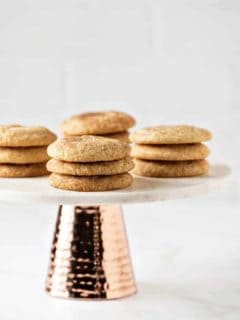 Side view of stacks of snickerdoodle cookies on a marbled cake stand