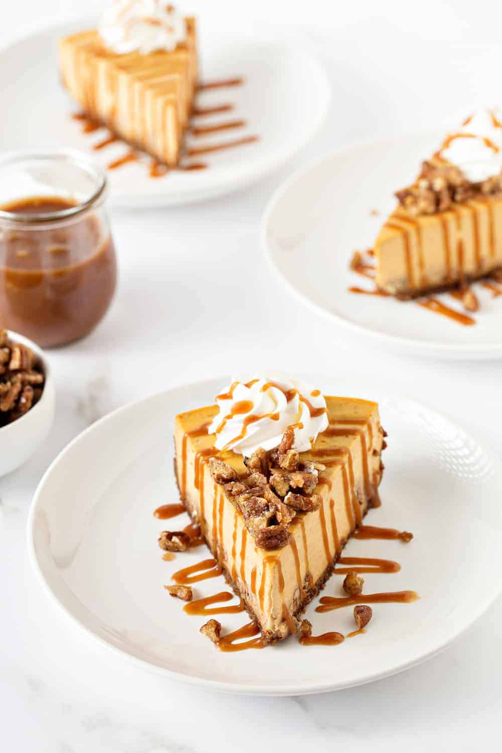Pumpkin Praline Cheesecake combines sweet praline pecans with creamy pumpkin cheesecake, a gingersnap crust and salted caramel sauce.